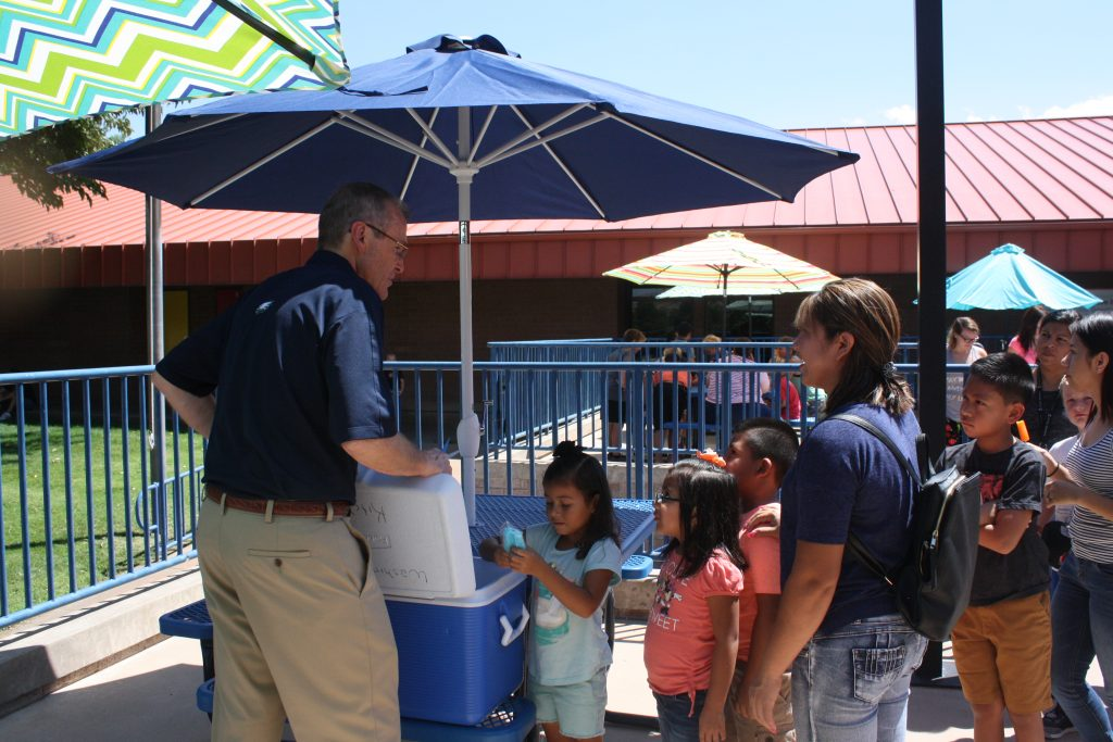 Principal handing out popsicles to students