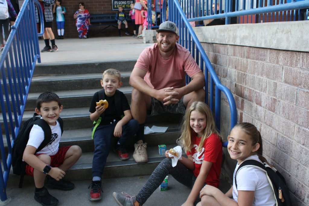 Students and parents enjoying time together and a donut