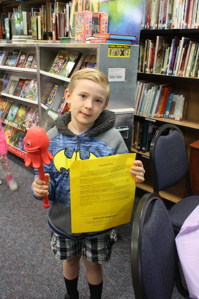 Student showing golden ticket for book fair
